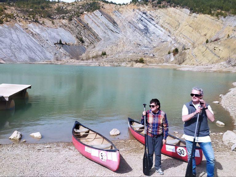 Imatge en que dues persones cegues sostenen el seu rem. Darrere seu veiem dues canoes amb les que han fet l'activitat al Llac de Tumí.