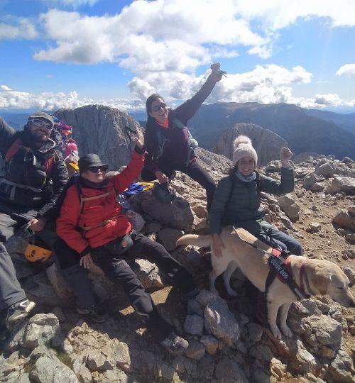 Imatge en que dues persones cegues, una amb gos pigall, acompanyades per dos guies al cim del Pedraforca, aixequen els punys en alt en senyal d'alegria per haver fet cim.