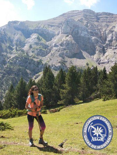 L'Àngels guia de muntanya en un prat amb les muntanyes del Cadí de fons. A la cantonada inferior dreta hi ha el logotip de l'Assosiació Espanyola de Guies de Muntanya.