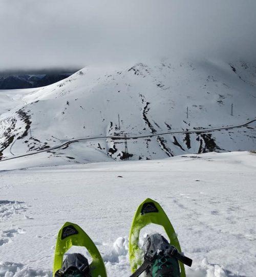 Paisatge de muntanya nevat amb unes raquetes de neu a primera plana.